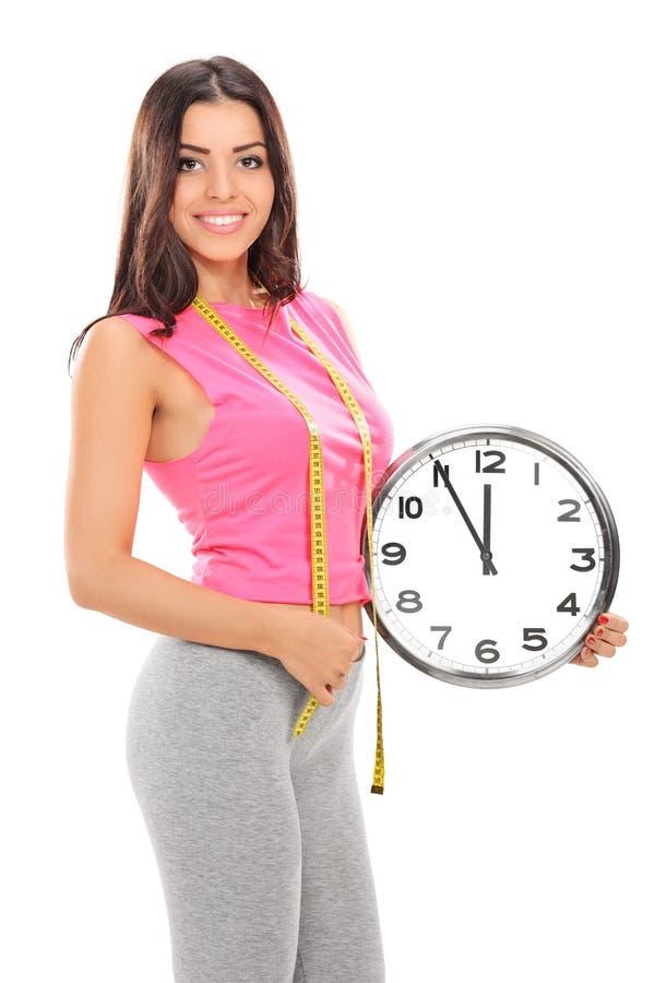 Mujer joven que sostiene un reloj de pared grande imagenes de archivo