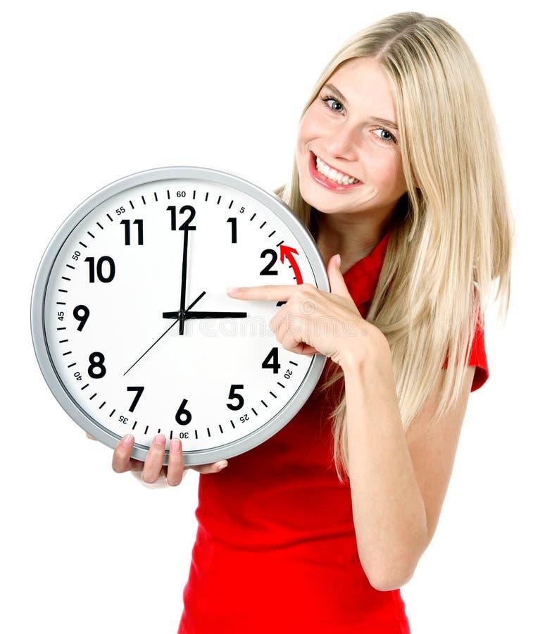 Mujer joven que sostiene un reloj. invierno fotografía de archivo libre de regalías