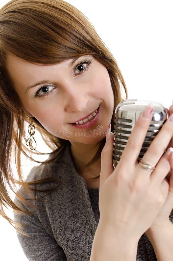Mujer joven que sostiene un retro-micrófono. imagen de archivo