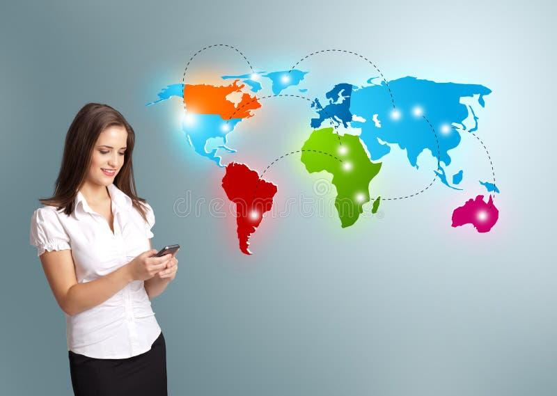 Mujer joven que sostiene un teléfono y que presenta el mapa del mundo colorido foto de archivo