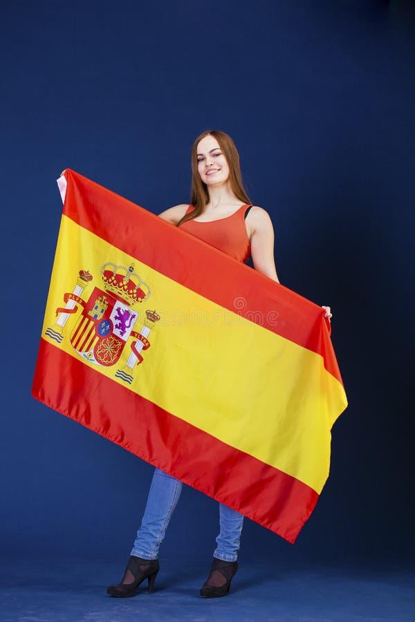 Mujer joven que sostiene una bandera española grande imágenes de archivo libres de regalías