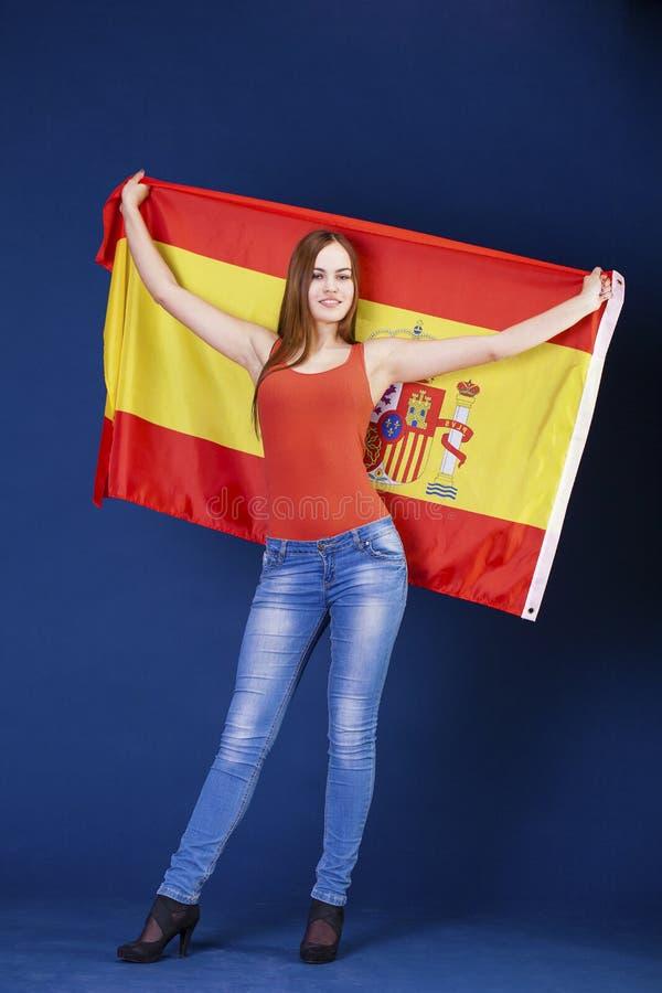 Mujer joven que sostiene una bandera española grande foto de archivo