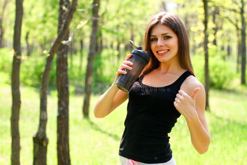 Mujer joven que sostiene una botella de agua y que hace los pulgares para arriba imagen de archivo libre de regalías