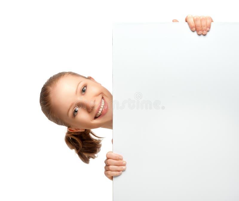 Mujer joven que sostiene una cartelera vacía en blanco blanca aislada imagen de archivo libre de regalías