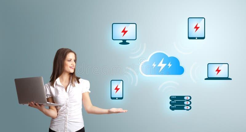 Mujer joven que sostiene una computadora portátil y que presenta el netw computacional de la nube imagen de archivo libre de regalías