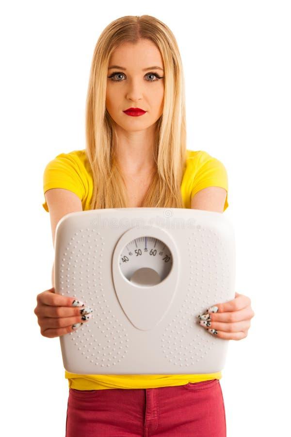 Mujer joven que sostiene una escala como gesto para flojo del peso aislada fotografía de archivo libre de regalías