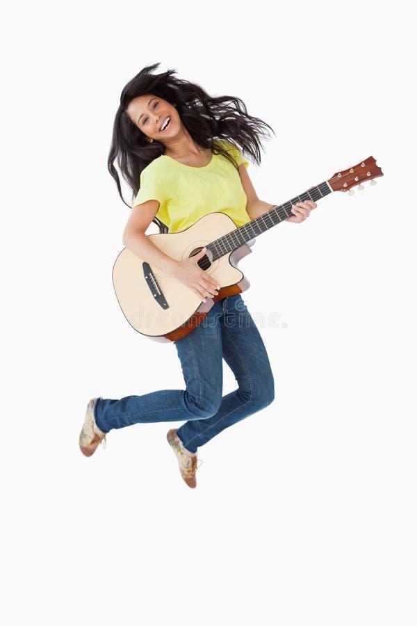 Mujer joven que sostiene una guitarra mientras que salta fotografía de archivo libre de regalías