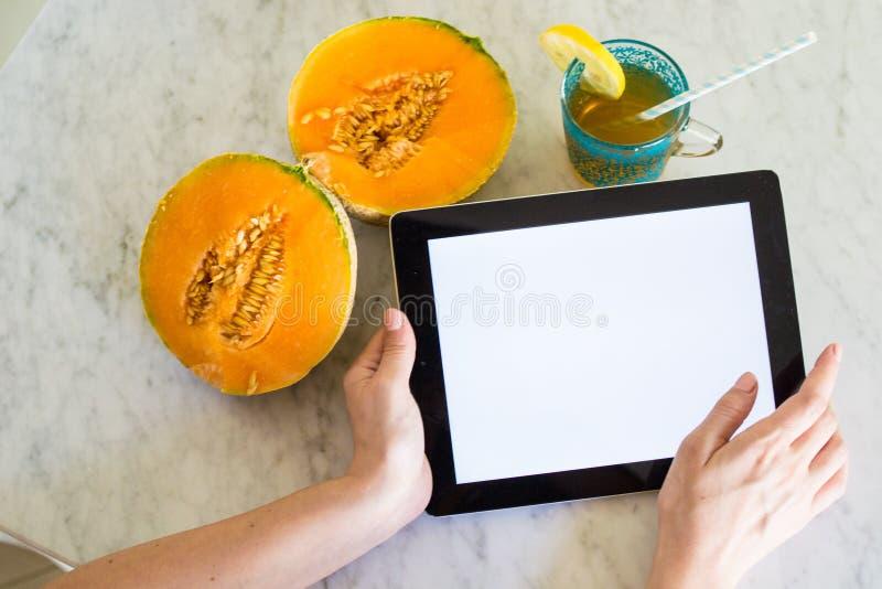 Mujer joven que sostiene una tableta con la pantalla de la maqueta con las manos en una tabla con la fruta y la bebida del verano imagen de archivo libre de regalías