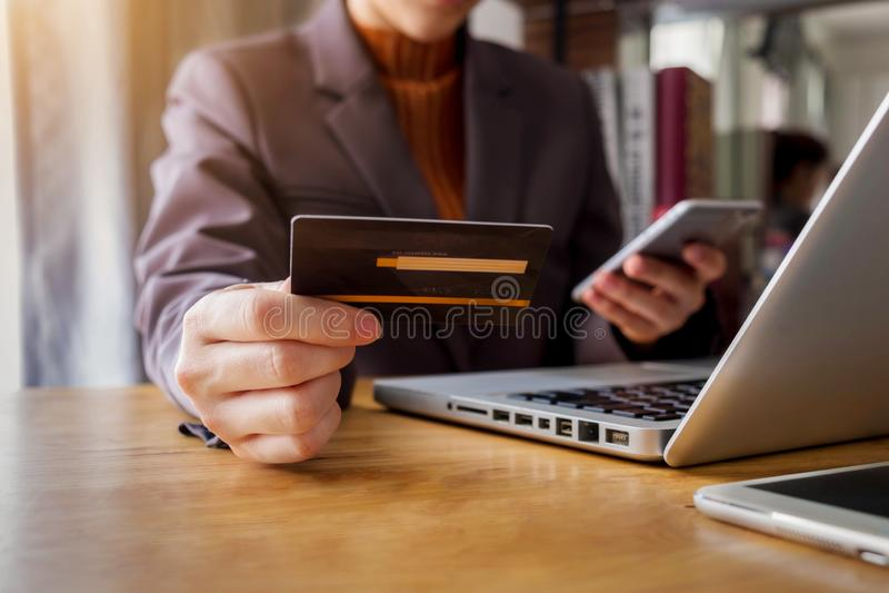 Mujer joven que sostiene una tarjeta de crédito para comprar compras en línea imagen de archivo