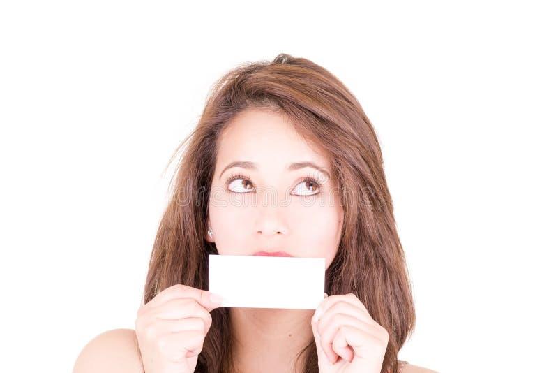 Mujer joven que sostiene una tarjeta de visita en blanco en frente foto de archivo