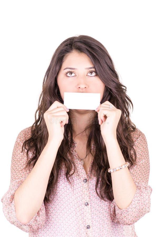 Mujer joven que sostiene una tarjeta de visita en blanco en frente fotos de archivo libres de regalías