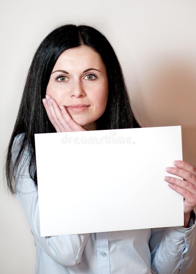 Mujer joven que sostiene una tarjeta vacía fotografía de archivo