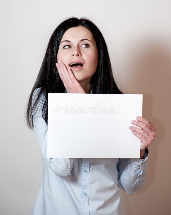 Mujer joven que sostiene una tarjeta vacía foto de archivo libre de regalías