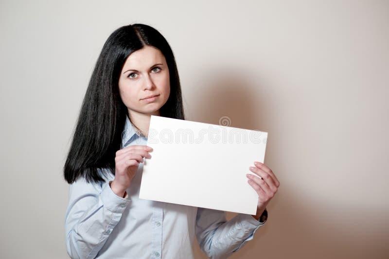 Mujer joven que sostiene una tarjeta vacía imagen de archivo libre de regalías