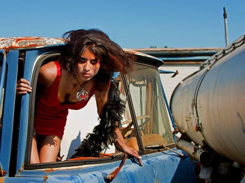 Mujer joven que sube fuera de un parabrisas imagenes de archivo