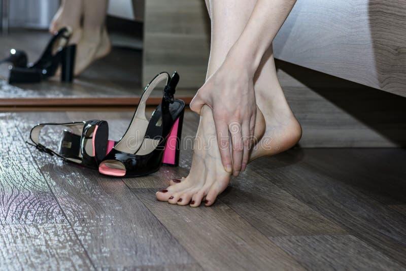 Mujer joven que sufre de dolor de piernas debido a los zapatos incómodos, tacones altos imagenes de archivo