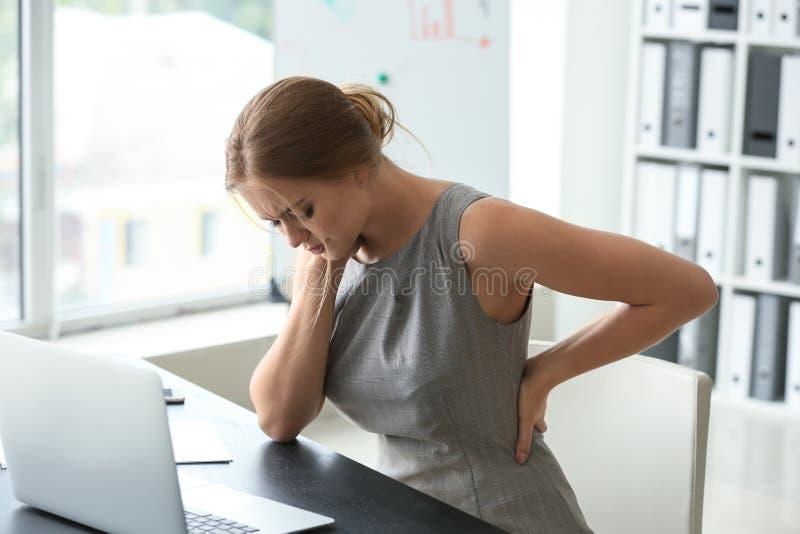 Mujer joven que sufre de dolor de espalda en oficina fotos de archivo