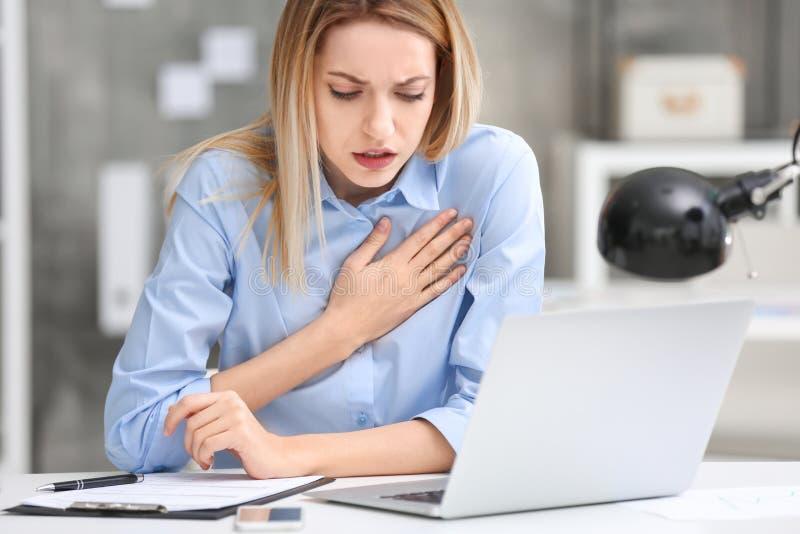 Mujer joven que sufre de dolor de pecho foto de archivo