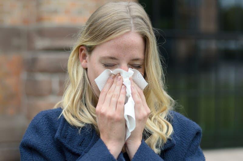Mujer joven que sufre de un frío estacional foto de archivo libre de regalías