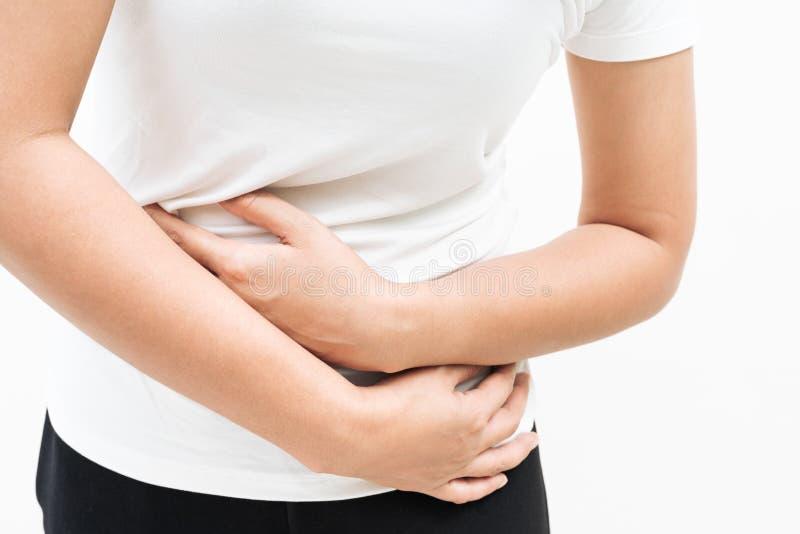 Mujer joven que sufre del dolor de estómago abdominal de la sensación del dolor, síntoma de pms en el fondo blanco foto de archivo