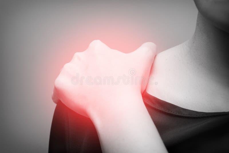 Mujer joven que sufre del dolor en hombro, dolor en el cuerpo humano en un fondo gris con el punto rojo blanco y negro fotografía de archivo