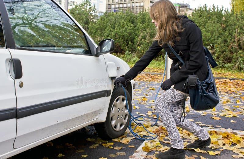 Mujer joven que tapa en un coche eléctrico foto de archivo