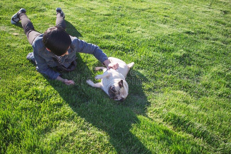 Mujer joven que tiene buen tiempo con barro amasado en la hierba verde, la muchacha bonita con el juego del perro en el parque du fotografía de archivo
