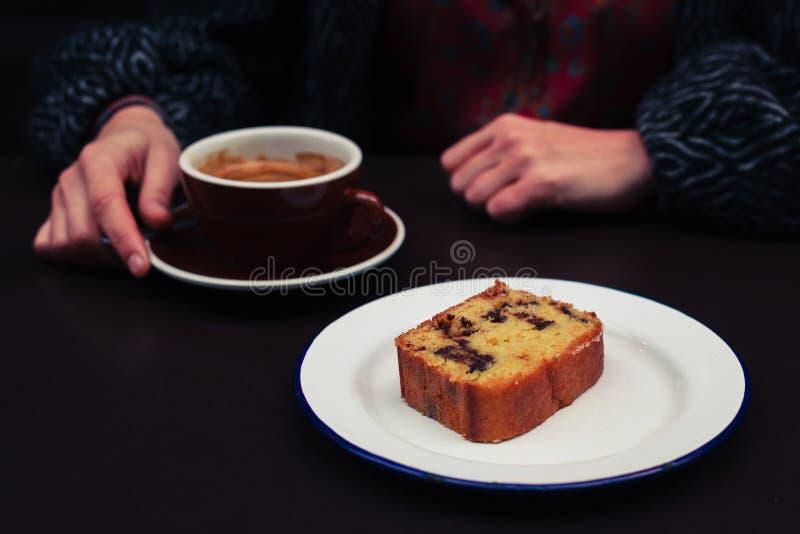 Mujer joven que tiene café y torta imagen de archivo libre de regalías
