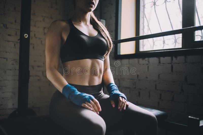 Mujer joven que tiene cierto resto después de entrenamiento duro en gimnasio fotografía de archivo libre de regalías