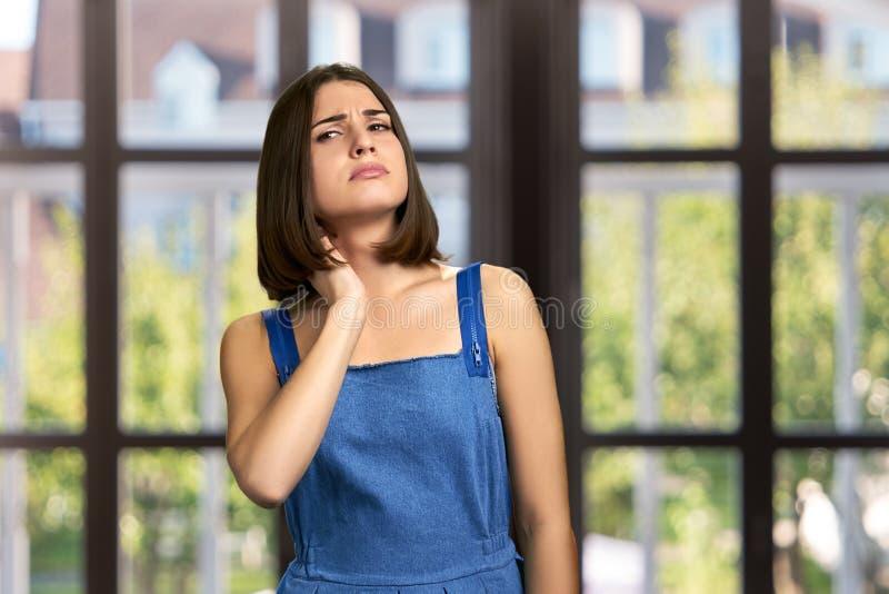 Mujer joven que tiene dolor de cuello fotografía de archivo