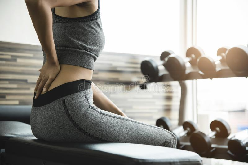Mujer joven que tiene dolor de espalda después de entrenamiento imagen de archivo