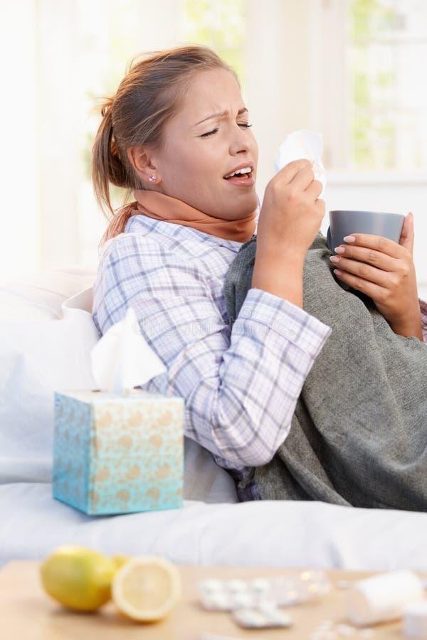 Mujer joven que tiene gripe el poner en la cama que estornuda imagen de archivo