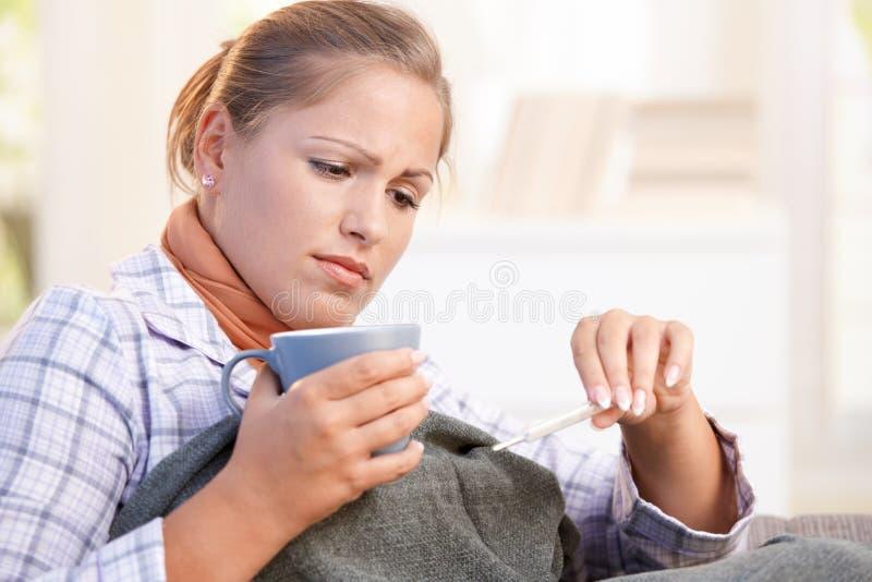 Mujer joven que tiene gripe el tomar de su temperatura fotografía de archivo libre de regalías