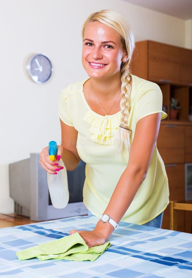 Mujer joven que tiene limpieza regular imagen de archivo