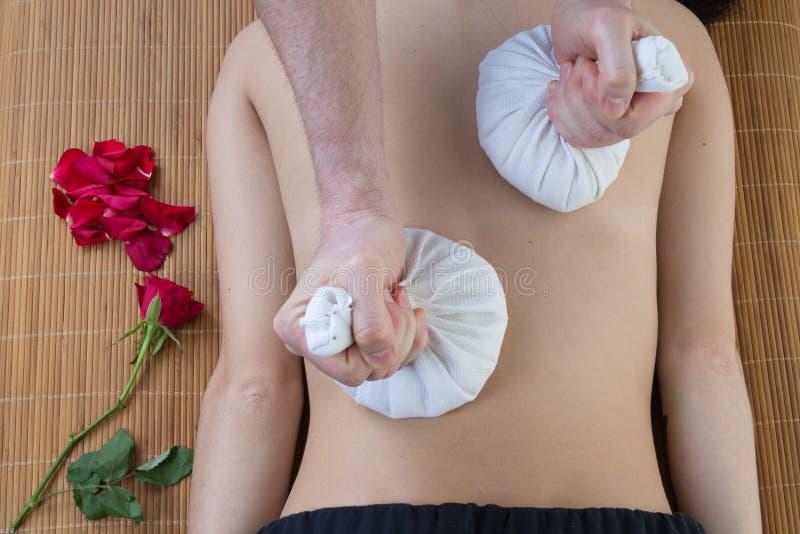 Mujer joven que tiene masaje con las bolas herbarias de la compresa en balneario foto de archivo libre de regalías
