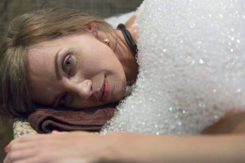 Mujer joven que tiene masaje de la espuma del jabón en hammam o baño turco imagen de archivo libre de regalías