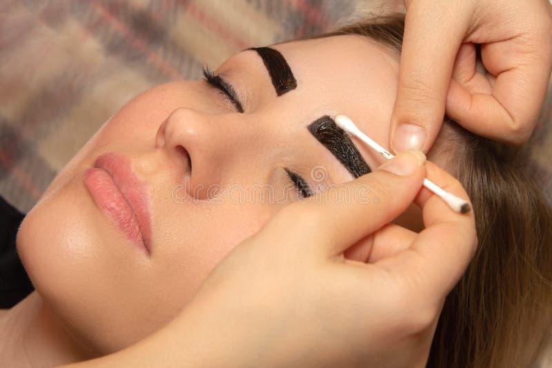 Mujer joven que tiene procedimiento profesional de la correcci?n de la ceja en sal?n de belleza imagenes de archivo