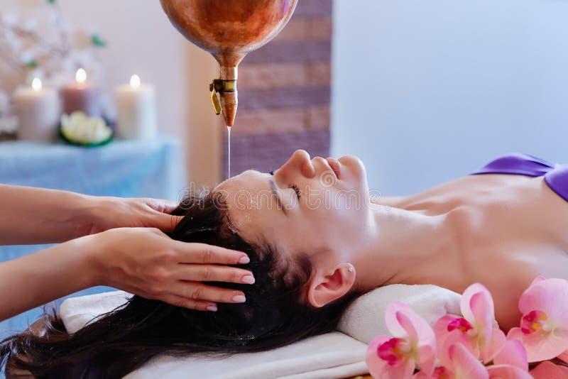 Mujer joven que tiene tratamiento de colada del balneario del masaje del aceite Shirodhar imagenes de archivo