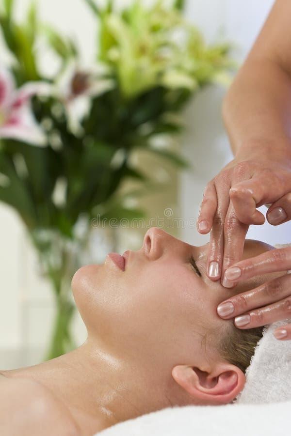 Mujer joven que tiene tratamiento facial del masaje imagen de archivo