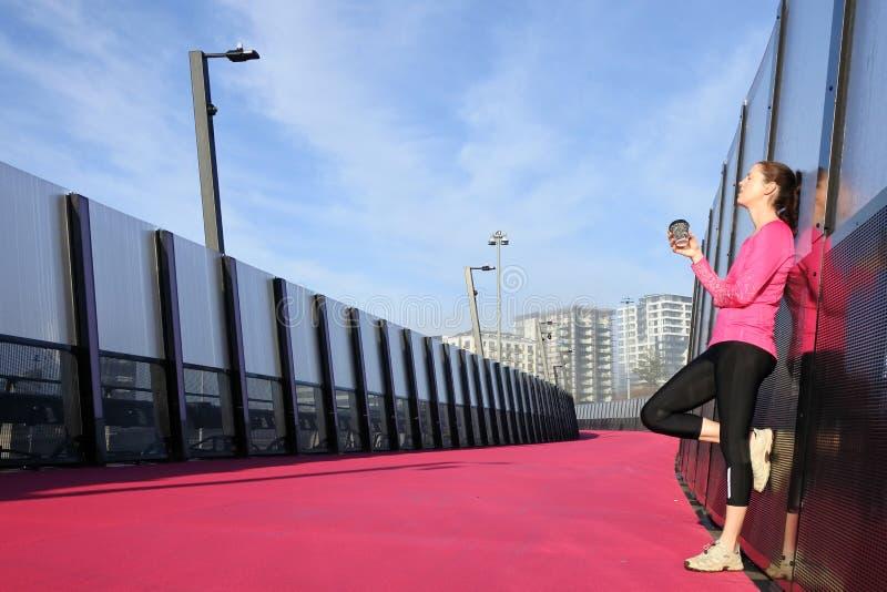 Mujer joven que tiene un descanso para tomar café en un camino rosado brillante fotos de archivo libres de regalías