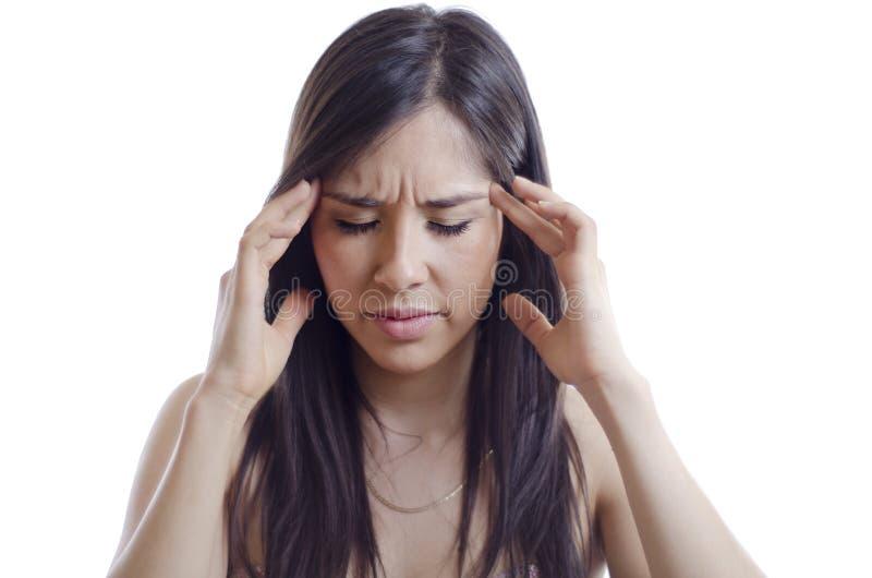Mujer joven que tiene un dolor de cabeza imagen de archivo