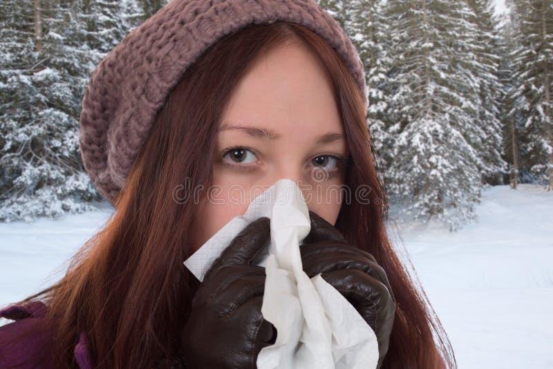Mujer joven que tiene un virus del frío y de la gripe al aire libre foto de archivo libre de regalías