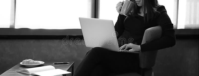 Mujer joven que tiene una taza de mujer de negocios del café con el ordenador portátil wo fotografía de archivo libre de regalías