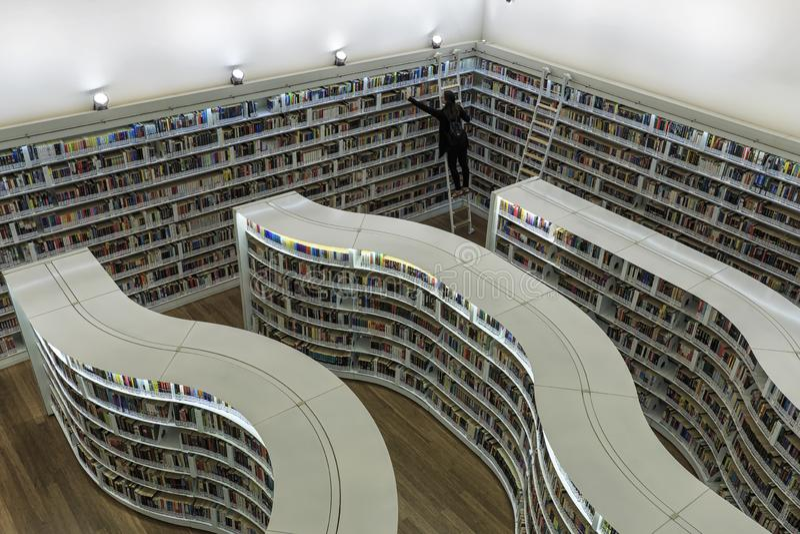 Mujer joven que tira de los libros de la biblioteca curvada de los estantes en la biblioteca en la alameda de la huerta foto de archivo libre de regalías