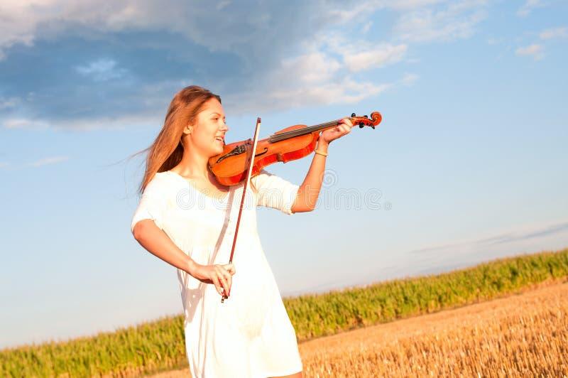 Mujer joven que toca el violín al aire libre imagen de archivo libre de regalías