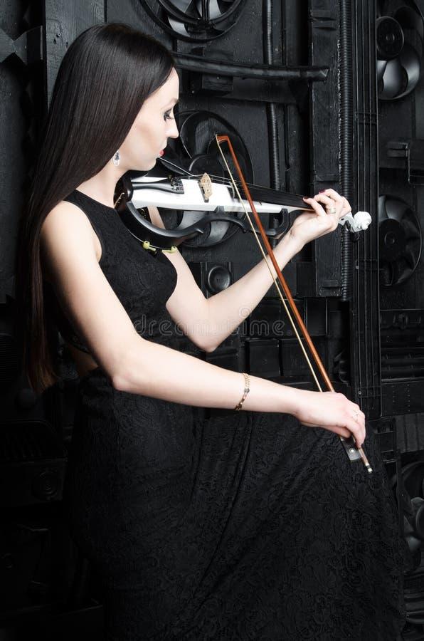 Mujer joven que toca el violín al lado de puertas del metal imagenes de archivo