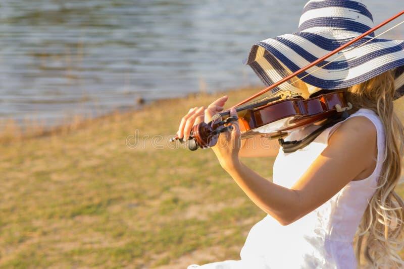 Mujer joven que toca el violín en fondo de la naturaleza fotos de archivo