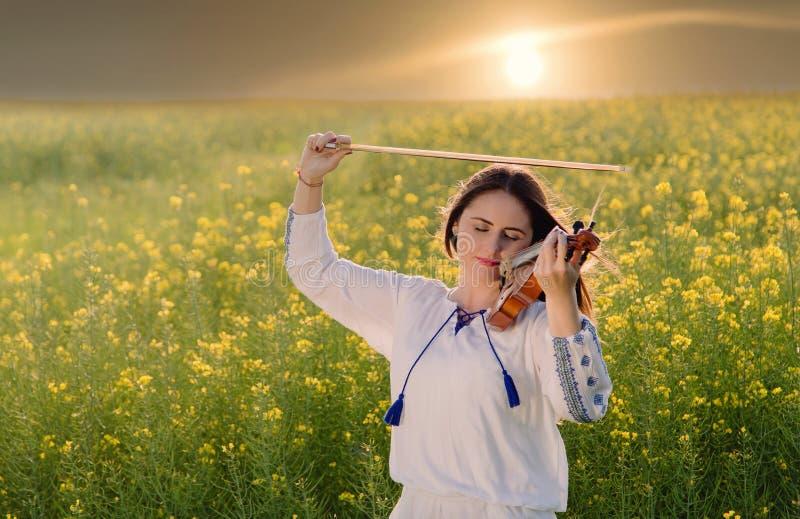 Mujer joven que toca el violín en un campo en la puesta del sol imagen de archivo libre de regalías