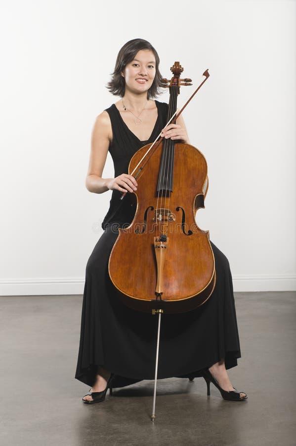 Mujer joven que toca el violoncelo foto de archivo libre de regalías