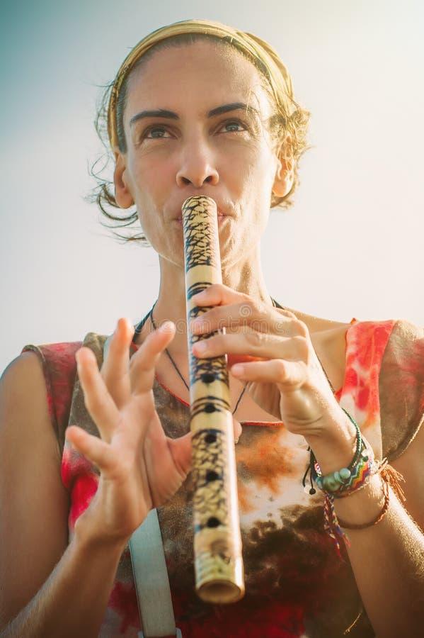 Mujer joven que toca la flauta de bambú el día de verano imagenes de archivo